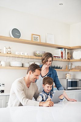 Buy stock photo Cropped shot of a young family of three using a tablet while sitting in the kitchen at home