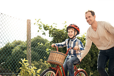 Buy stock photo Cropped shot of an adorable little boy learning how to ride a bike with his father outside