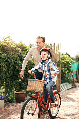 Buy stock photo Full length shot of an adorable little boy learning how to ride a bike with his father outside