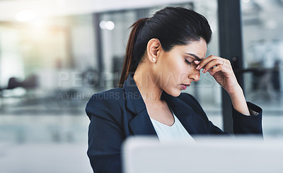 Buy stock photo Cropped shot of an attractive young businesswoman experiencing a headache in her office
