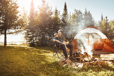 Buy stock photo Shot of a young Dad and his son camping in the forest
