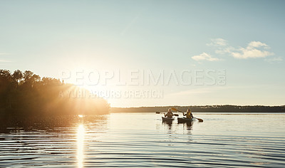 Buy stock photo Shot of a young couple kayaking on a lake outdoors