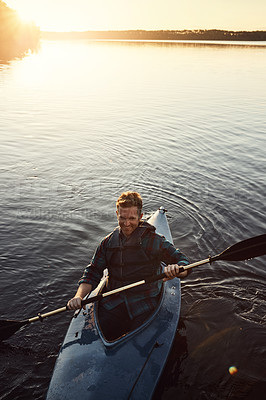 Buy stock photo High angle shot of a young man kayaking on a lake outdoors