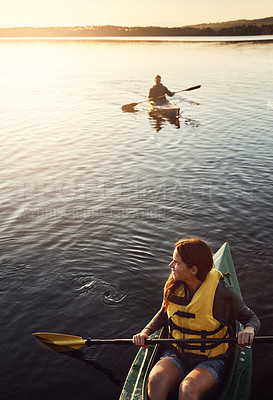 Buy stock photo High angle shot of a young couple kayaking on a lake outdoors