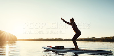 Buy stock photo Shot of an attractive young woman doing yoga on a paddle board on a lake outdoors