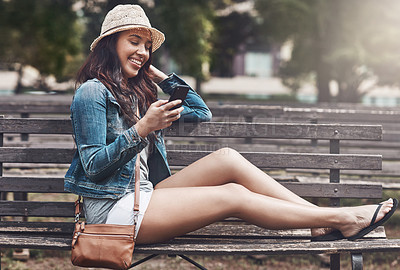 Buy stock photo Shot of an attractive young woman using a cellphone at the park