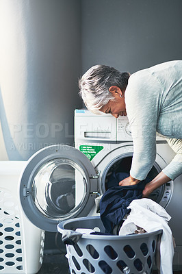 Buy stock photo Shot of a mature woman doing laundry at home