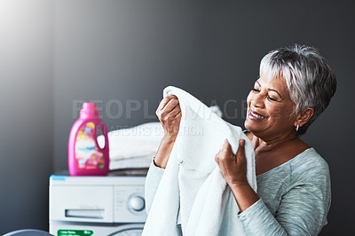 Buy stock photo Shot of a mature woman smelling freshly washed towels while doing laundry at home