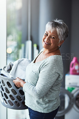 Buy stock photo Portrait of a mature woman doing laundry at home