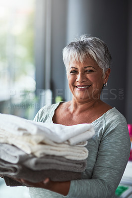 Buy stock photo Portrait of a mature woman holding freshly folded towels while doing laundry at home