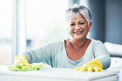 Buy stock photo Portrait of a happy mature woman wearing rubber gloves while cleaning a table at home