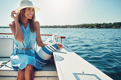 Buy stock photo Shot of an attractive young woman spending the day on her private yacht