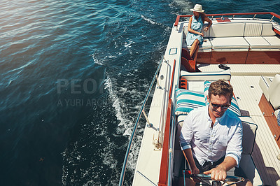 Buy stock photo High angle shot of a handsome young man steering a yacht with his wife sitting in the background