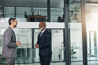 Buy stock photo Shot of two businessmen having a discussion in an modern office
