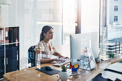 Buy stock photo Cropped shot of an attractive businesswoman working  on her computer at her desk
