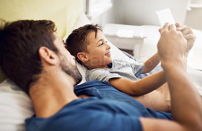 Buy stock photo Shot of a young man using a digital tablet with his son at home
