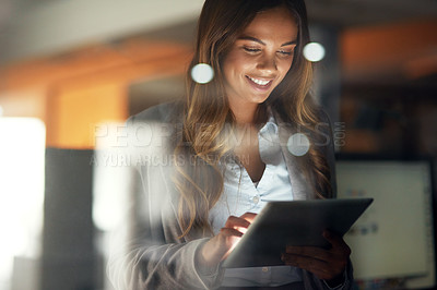 Buy stock photo Shot of a young attractive businesswoman working late at night in a modern office