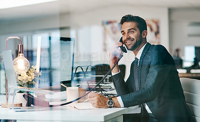 Buy stock photo Shot of a cheerful young businessman making a call while being seated inside of the office