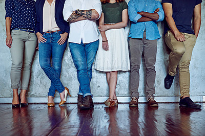 Buy stock photo Shot of an unrecognizable group of businesspeople standing against a wall in an office