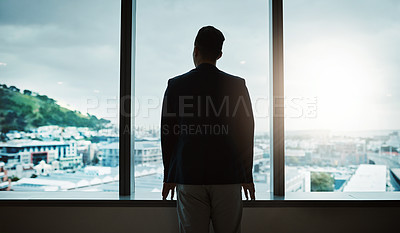 Buy stock photo Rearview shot of a young businessman looking thoughtfully out of an office window