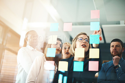 Buy stock photo Shot of a group of businesspeople arranging sticky notes on a glass wall in a modern office