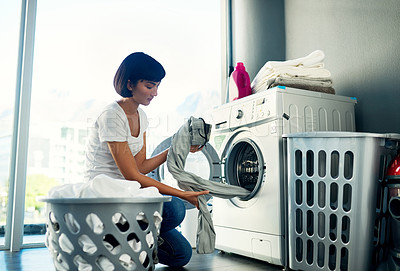 Buy stock photo Shot of a young woman doing her laundry at home