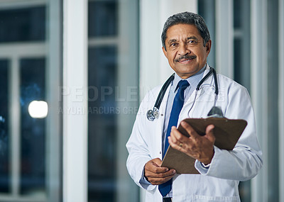 Buy stock photo Portrait of a happy mature doctor holding a clipboard in a hospital