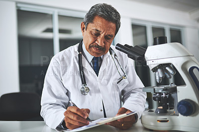 Buy stock photo Shot of a mature scientist using a microscope and recording his findings in a laboratory