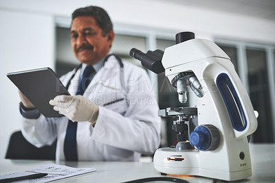 Buy stock photo Shot of a microscope on a laboratory table with a scientist using a digital tablet in the background