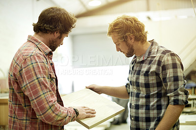 Buy stock photo Shot of two men looking at a sample of wood in their workshop