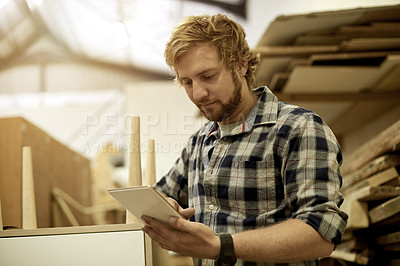 Buy stock photo Cropped shot of a craftsman using his digital tablet in his workshop