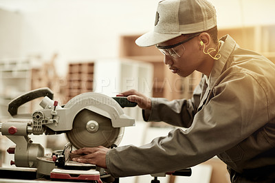 Buy stock photo Cropped shot of a handsome young carpenter cutting wood in his workshop