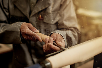 Buy stock photo Cropped shot of an unrecognizable male carpenter chiselling away on a piece of wood in his workshop