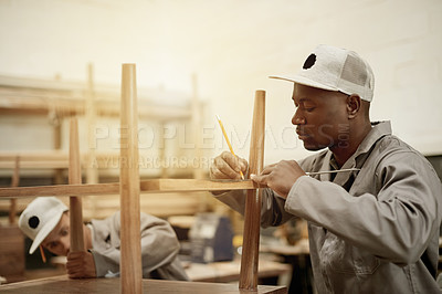 Buy stock photo Cropped shot of a handsome male carpenter putting together a wood piece in his workshop