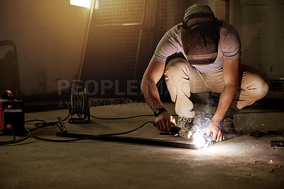 Buy stock photo Full length shot of an unrecognizable young welder working in his workshop