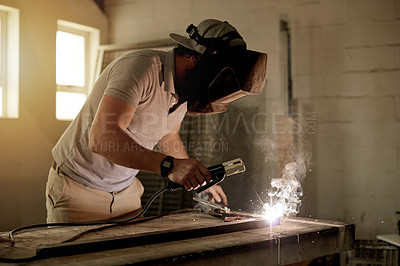 Buy stock photo Cropped shot of an unrecognizable young welder working in his workshop