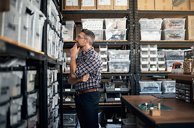 Buy stock photo Shot of a man looking through the shelves in a workshop
