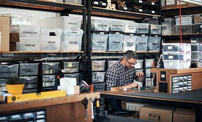 Buy stock photo Shot of a middle aged man manufacturing something in a workshop