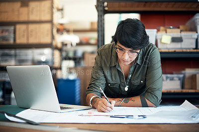 Buy stock photo Shot of a woman using a laptop while working on a project in a workshop