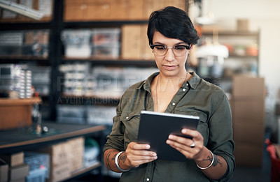 Buy stock photo Shot of a woman using a digital tablet in a workshop