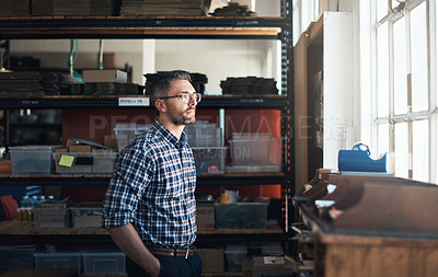 Buy stock photo Shot of a thoughtful man working in a workshop