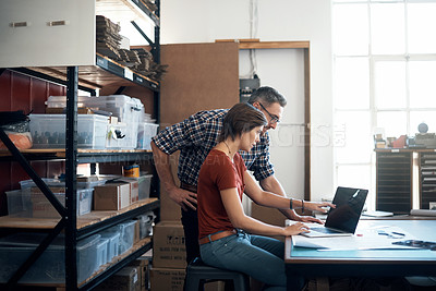 Buy stock photo Shot of a man and woman using a laptop while working on a project together in a workshop