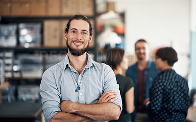 Buy stock photo Portrait of a confident man in a workshop with his colleagues working in the background