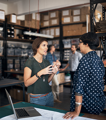 Buy stock photo Shot of two women working on a project together in a workshop