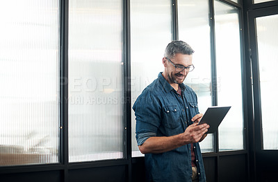 Buy stock photo Shot of a mature designer using a digital tablet in an office