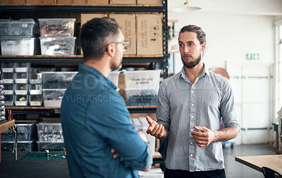 Buy stock photo Shot of two men having a discussion in a workshop