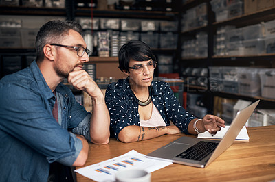 Buy stock photo Shot of two colleagues using a laptop in a workshop