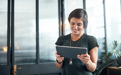Buy stock photo Shot of a young designer using a digital tablet in an office