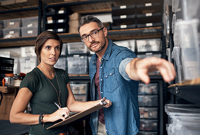 Buy stock photo Shot of two colleagues working together in a workshop
