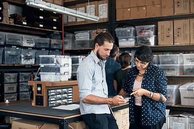 Buy stock photo Shot of two colleagues using a cellphone in a workshop